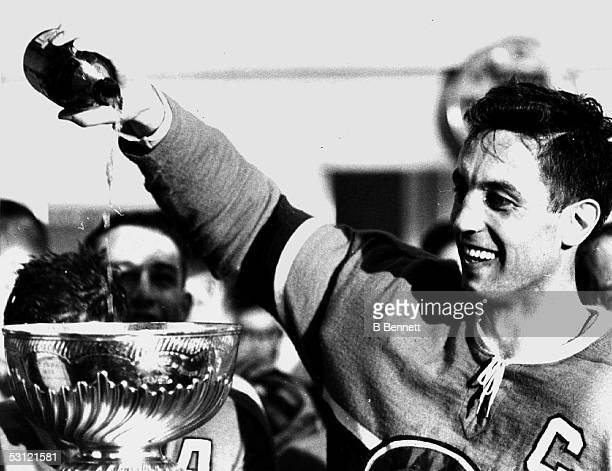 Jean Beliveau of the Montreal Canadiens pours champagne into the Stanley Cup Trophy after the Canadiens defeated the Chicago Blackhawks by a score of...