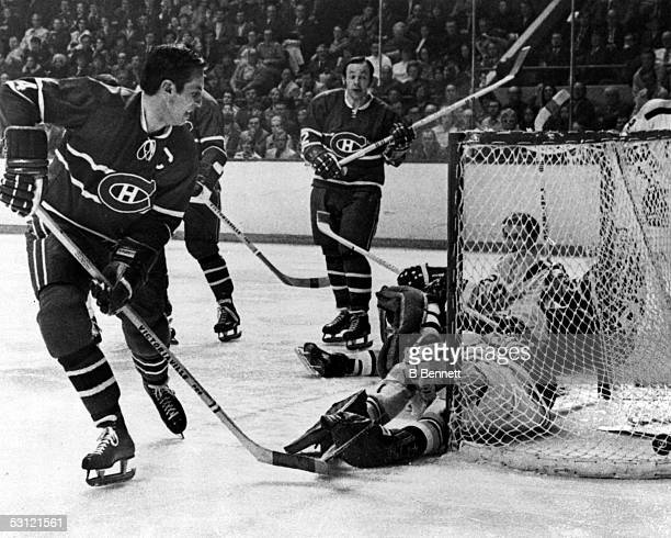 Jean Beliveau of the Montreal Canadiens scores on goalie Ed Johnston of the Boston Bruins as Beliveau's teammate Yvan Cournoyer looks on during Game...