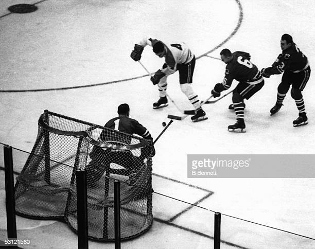 Jean Beliveau of the Montreal Canadiens scores on goalie Glenn Hall of the Chicago Blackhawks as his teammates Reg Fleming and Pierre Pilote try to...