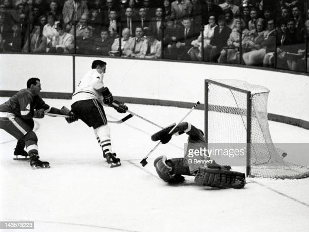 Jean Beliveau of the Montreal Canadiens scores on the breakaway past goalie Roger Crozier and Bill Gadsby of the Detroit Red Wings during Game 3 of...