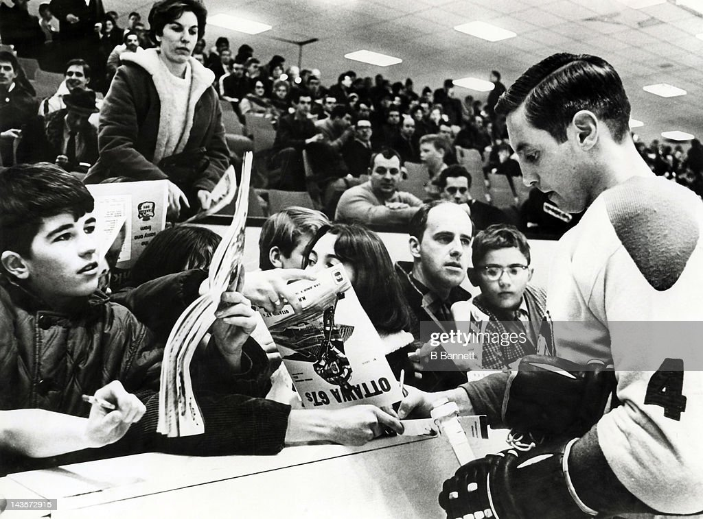 Jean Beliveau #4 of the Montreal Canadiens signs autographs for kids before the charity game between the Canadiens and the Ottawa 67's of the Ontario Hockey League on January 22, 1968 at the Ottawa Civic Centre in Ottawa, Ontario, Canada.