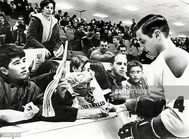 Jean Beliveau of the Montreal Canadiens signs autographs for kids before the charity game between the Canadiens and the Ottawa 67's of the Ontario...