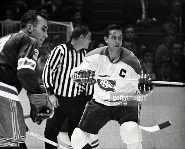 Jean Beliveau of the Montreal Canadiens skates on the ice as he is defended by Harry Howell of the New York Rangers on October 24 1965 at the Madison...