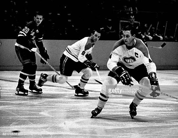 Jean Beliveau of the Montreal Canadiens skates towards the puck as teammate Bill Hicke gets back on defense against Phil Goyette of the New York...