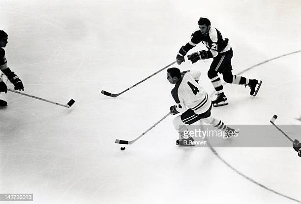 Jean Beliveau of the Montreal Canadiens skates with the puck as Danny Grant of the Minnesota North Stars defends circa 1971 at the Montreal Forum in...