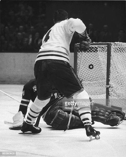 Jean Beliveau of the Montreal Canadiens treis to knock the puck past the unidentified goalkeeper for the New York Rangers circa 1960's at the Madison...