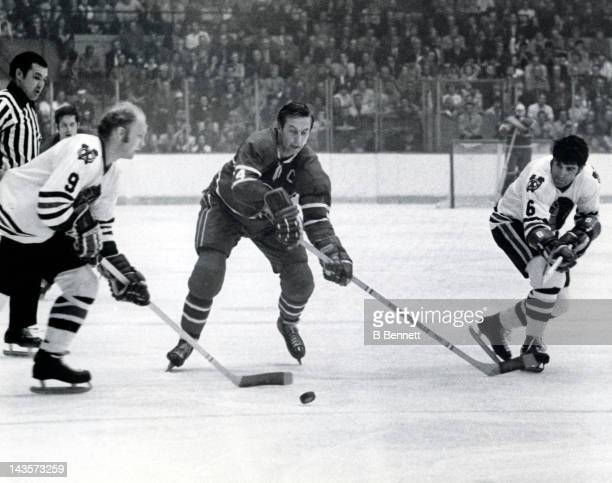 Jean Beliveau of the Montreal Canadiens tries to go for the puck as Bobby Hull and Lou Angotti of the Chicago Blackhawks take control during Game 7...