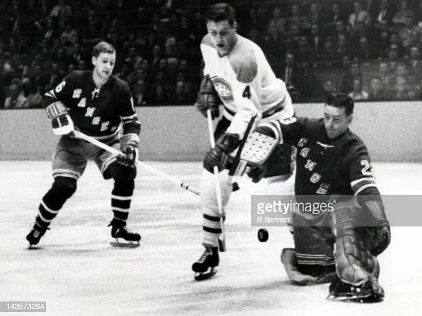 Jean Beliveau of the Montreal Canadiens tries to score on goalie Marcel Paille of the New York Rangers as his teammate Rod Seiling looks on during...