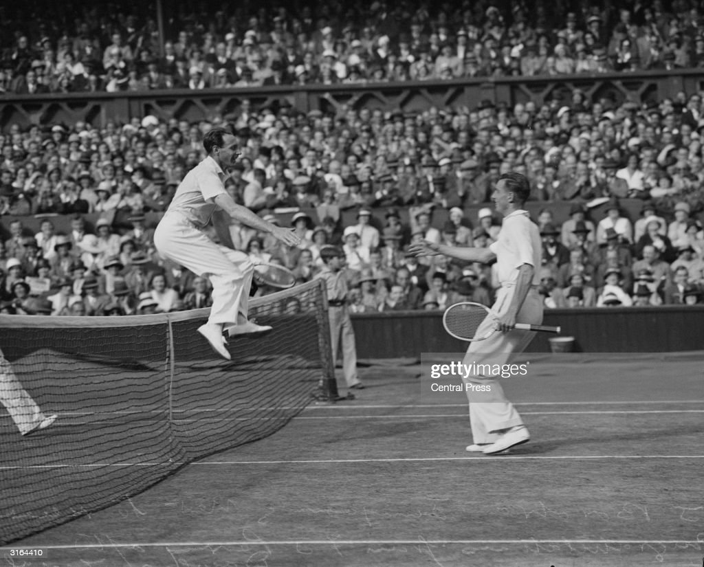English tennis champion Fred Perry (1909 - 1995) leaping over the net to shake hands with his opponent after winning the Wimbledon men's singles final.