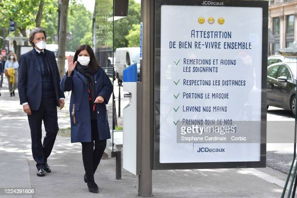 Jean Charles Decaux and Paris Mayor Anne Hidalgo wearing a protective facemask salutes as she arrives to inaugurate a public hydroalcoholic gel...