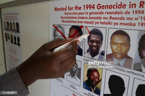 Jean Claude Ndatabaye administrative secretary of the Genocide Fugitive Tracking Unit draws a red cross on the face of Augustin Bizimana one of the...