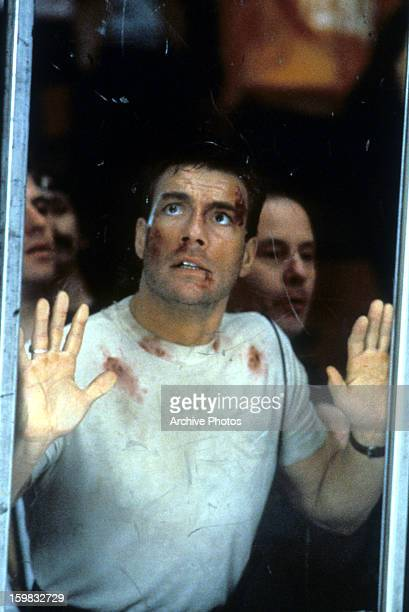 Jean Claude Van Damme puts his hands against glass in a scene from the film 'Sudden Death', 1995.
