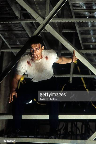 Jean Claude Van Damme sits in the rafters in a scene from the film 'Sudden Death', 1995.