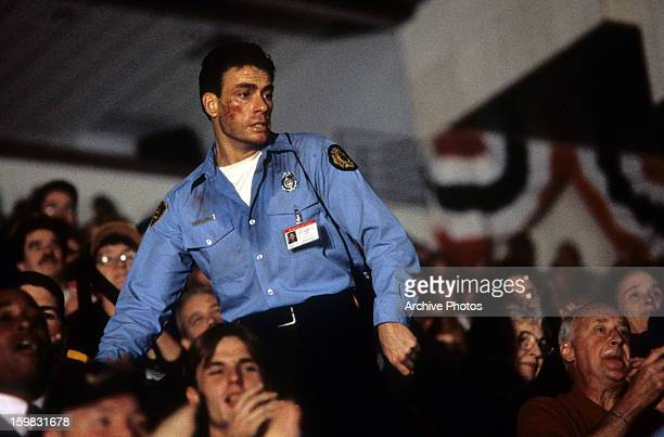 Jean Claude Van Damme stands over the crowd in a scene from the film 'Sudden Death', 1995.