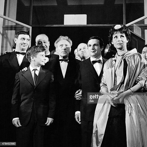 Jean Cocteau and Francois Truffaut surrounded with the team of the movie 400 knocks at the exit of the Palace of the Cannes film festival