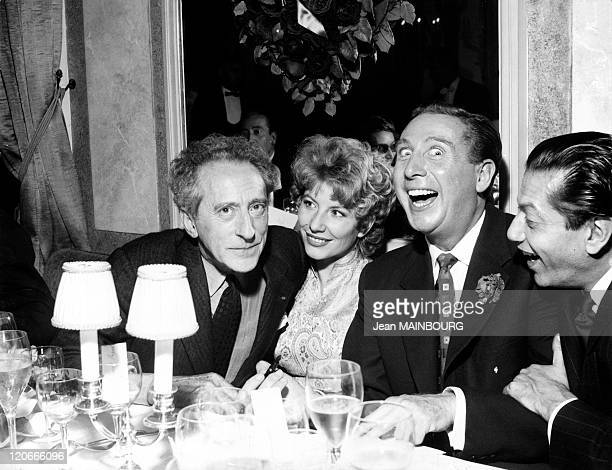 Jean cocteau in Paris France in October 1955 Jean cocteau Jacqueline Pagnol and Charles Trenet at Maxim's to celebrate the golden album obtained by...