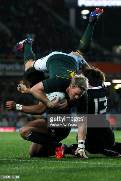 Jean de Villiers of South Africa charges over Julian Savea and Conrad Smith of New Zealand during The Rugby Championship match between the New...