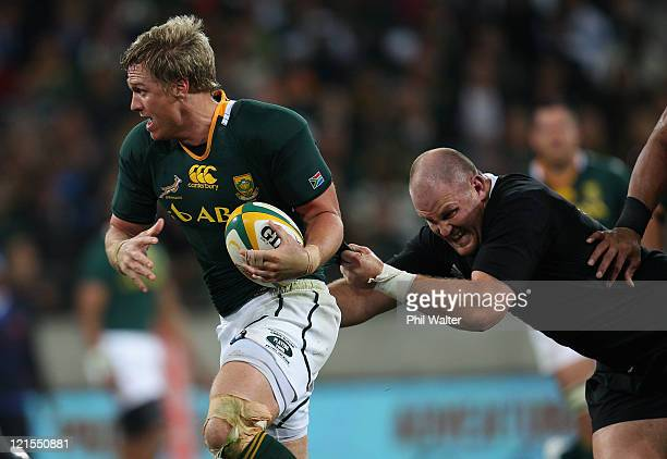 Jean de Villiers of the Springboks is tackled by Ben Franks of the All Blacks during the Tri Nations Test match between the South African Springboks...