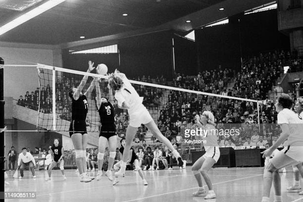 Jean Gaertner of the United States attempts to spike the ball against the defence of Ryong Ja Kwak and Chung Ja Oh of South Korea during the Women's...