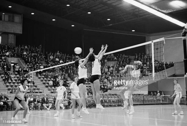 Jean Gaertner of the United States attempts to spike the ball against the defence of Doina Popescu and Ileana Enculescu of Rumania during their...