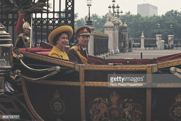 Jean, Grand Duke of Luxembourg rides with Queen Elizabeth II in an open carriage through the gates of Buckingham Palace, at the start of a four-day...