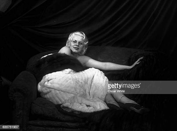 Jean Harlow an American actress who was the sex symbol of the 1930s reclines on a coach draped with furs