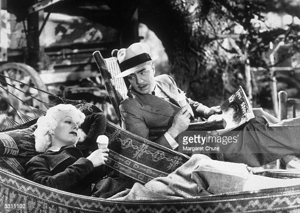 Jean Harlow eats an icecream next to William Powell in a scene from the film 'Reckless'