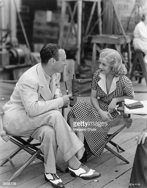 Jean Harlow talks over the next scene for 'Riff Raff' with director J Walter Ruben A film produced by Irving G Thalberg for MGM