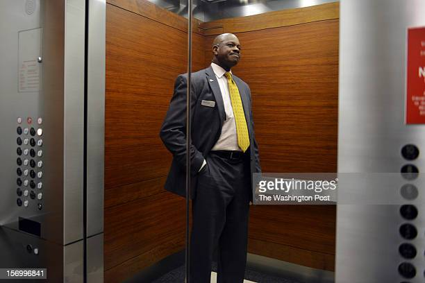 Jean Kabre takes an elevator to the floor of his office where he works as a concierge and event planner at 101 Constitution Avenue on Tuesday...