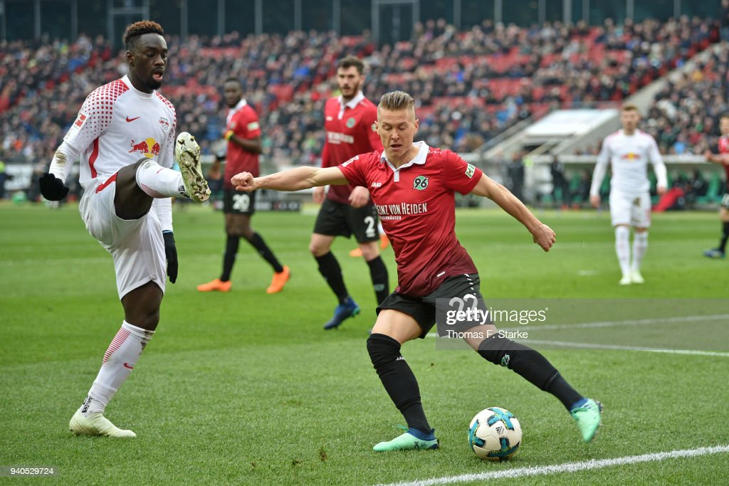 Jean - Kevin Augustin (L) of Leipzig and Matthias Ostrzolek of Hannover fight for the ball during the Bundesliga match between Hannover 96 and RB Leipzig at HDI-Arena on March 31, 2018 in Hanover, Germany.