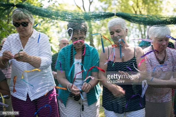 Jean Leadbeater the mother of murdered Member of Parliament Jo Cox joins others in symbolically tying a ribbon onto a piece of netting during a...