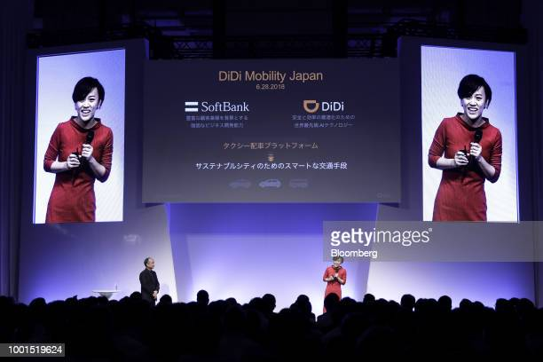 Jean Liu president of Didi Chuxing right speaks as Masayoshi Son chairman and chief executive officer of SoftBank Group Corp looks on at the SoftBank...
