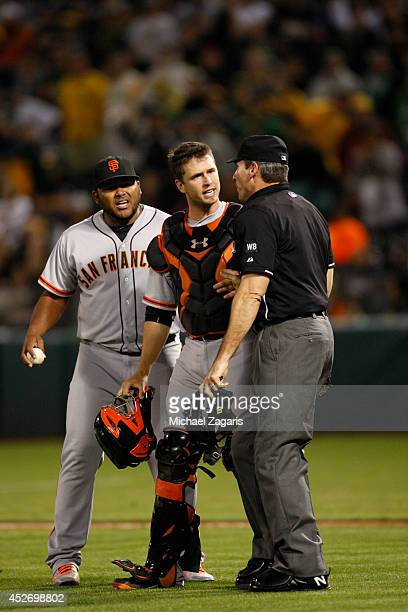 Jean Machi and Buster Posey of the San Francisco Giants questions Umpire Angel Hernandez on a called balk during the game against the Oakland...
