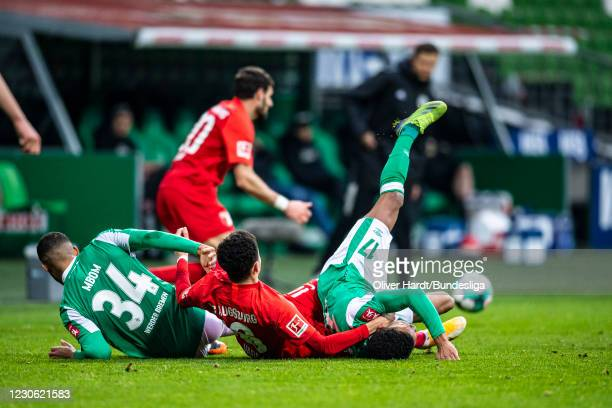 Jean Manuel Mbom and Felix Agu of SV Werder Bremen competes for the ball with Rubens Estephan Vargas Martinez of FC Augsburg during the Bundesliga...