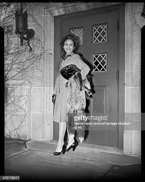 Jean Mason holding fox stole standing in front of door to the University of Pittsburgh's Falk School Pittsburgh Pennsylvania March 1946