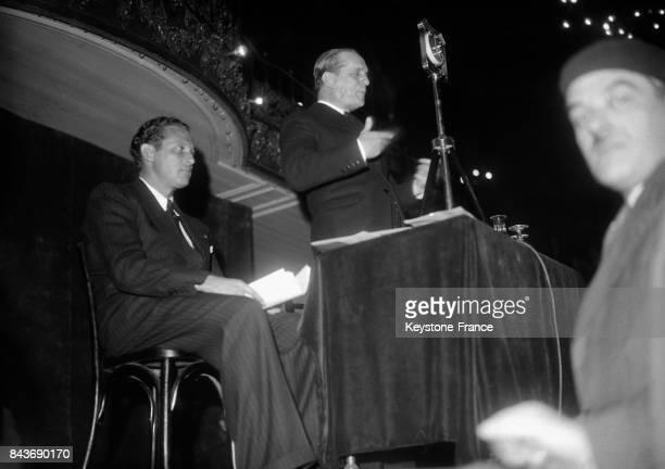 Jean Mermoz, assis, à gauche, lors d'une conférence des 'Croix de feu', salle Wagram, à Paris, France, le 31 mars 1936.