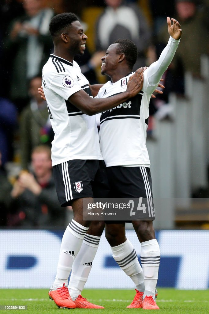 Jean Michael Seri of Fulham celebrates with teammate Timothy Fosu-Mensah after scoring his team's first goal during the Premier League match between Fulham FC and Burnley FC at Craven Cottage on August 26, 2018 in London, United Kingdom.