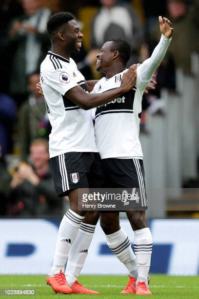 Jean Michael Seri of Fulham celebrates with teammate Timothy FosuMensah after scoring his team's first goal during the Premier League match between...