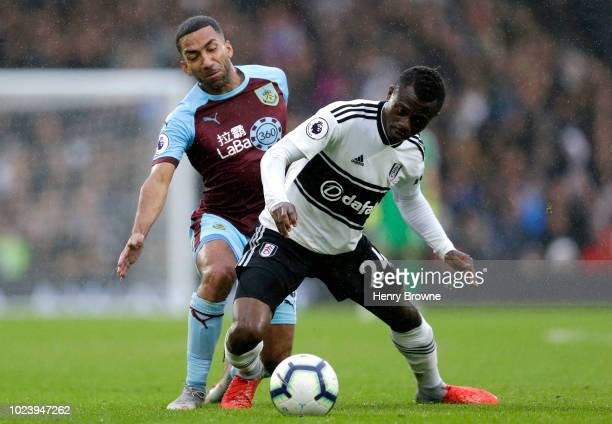 Jean Michael Seri of Fulham is challenged by Aaron Lennon of Burnley during the Premier League match between Fulham FC and Burnley FC at Craven...