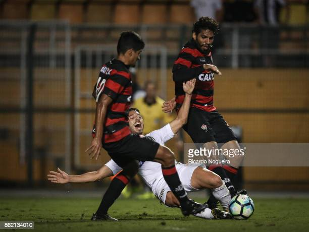 Jean Mota of Santos battles for the ball with Wallace and Ramon of Vitoria during the match between Santos and Vitoria as a part of Campeonato...
