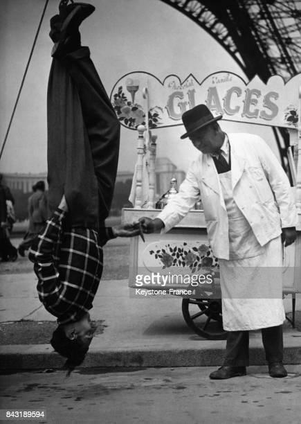Jean Murtyl acrobate suspendu par les pieds à une dépanneuse s'arrête sous la Tour Eiffel pour acheter une glace à un glacier à Paris France