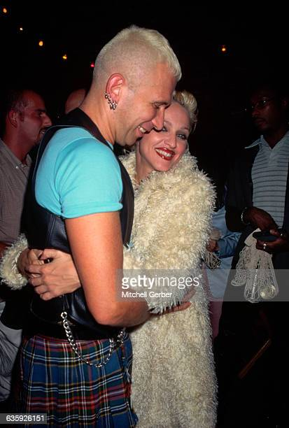 Jean Paul Gaultier wearing a kilt smiles as he hugs Madonna who wears a fake fur coat