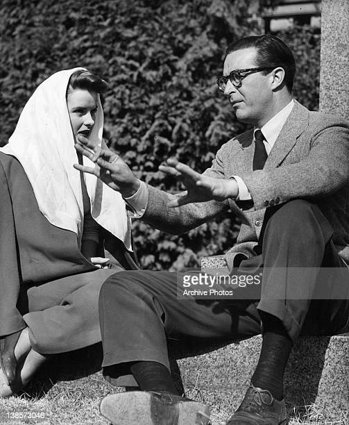 Jean Peters with scarf on head sits with Ray Milland on steps in a scene from the film 'It Happens Every Spring', 1949.