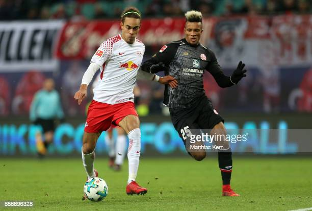 Jean Philippe Gbamin of Mainz battles for the ball with Yussuf Poulsen of Leipzig during the Bundesliga match between RB Leipzig and 1FSV Mainz 05 at...