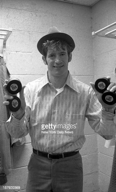 Jean Ratelle of the N Y Rangers holds four pucks to show that he pulled the hat trick plus one when he scored four goals at Madison Square Garden