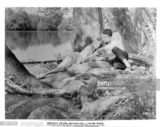 Jean Seberg sharing romantic moment with Warren Beatty at the trunk of a tree in a scene from the film 'Lilith', 1964.
