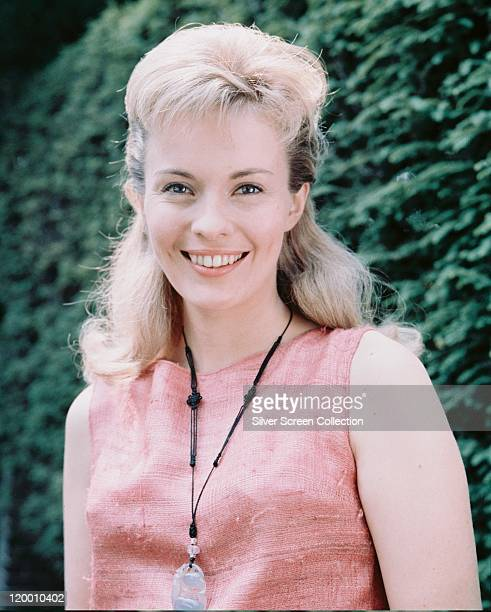 Jean Seberg , US actress, smiling, wearing a pink sleeveless top and a black necklace with a large metal pendant, against a green background, circa...