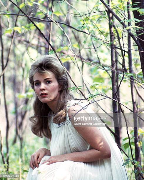 Jean Seberg US actress wearing a white dress as she sits among trees and foliage circa 1970