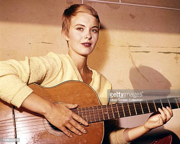 Jean Seberg , US actress, wearing a yellow jumper as she plays an acoustic guitar, circa 1970.