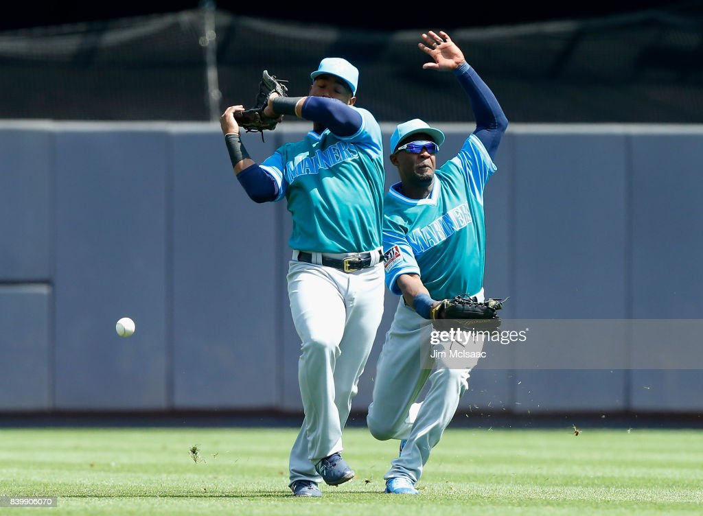 Jean Segura #2 (L) and Guillermo Heredia #5 of the Seattle Mariners can't come up with a ball hit by Gary Sanchez of the New York Yankees during the first inning at Yankee Stadium on August 27, 2017 in the Bronx borough of New York City.